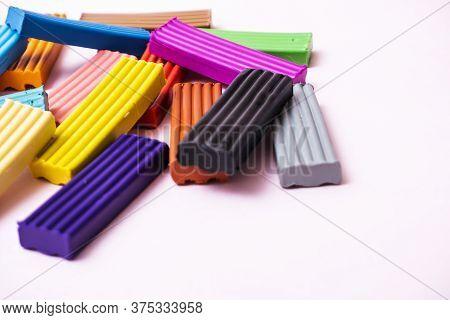 Plates Of Multi-colored Plasticine. Photo Of Plasticine On A Pink Background.
