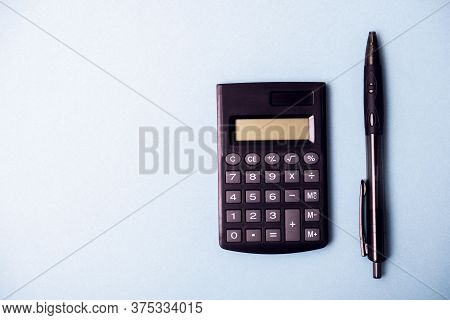 Photo Of A Calculator And Pens On A Blue Background. Desktop Calculator. Bookkeeping Background.