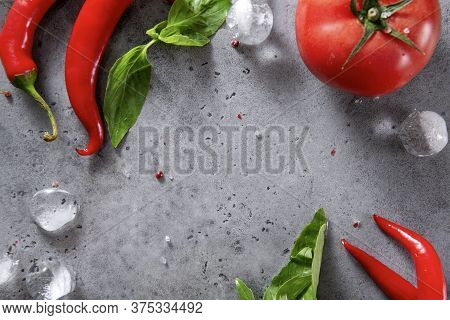 1  Red Tomato, Green Basil Sprigs, Salt,  Ice Cubes , Red Chili Peppers,  Spices  On A Gray ,  Copy