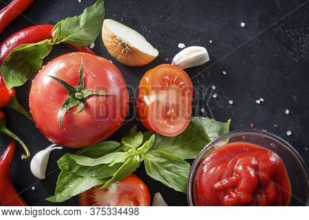 Whole And Pieces Of Ripe Red Tomatoes, Chili Peppers, Green Basil Sprigs, Garlic, Spices On A Black