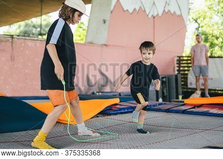 Two Little Boys Jumping On Trampoline In Sport Center. Kids Having Fun Together. Active Leisure. Chi