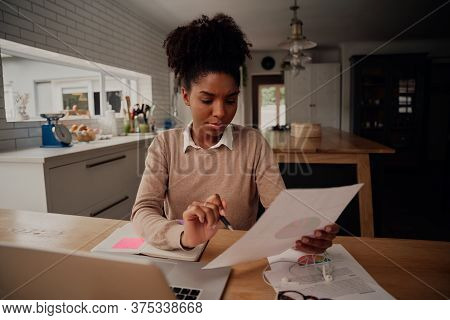 Young Female Freelancer Analysing Documents And Comparing Growth While Working On Laptop At Home Dur
