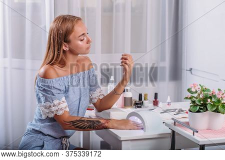 Beautiful Girl With Tattoo Sits At The Table And Dries Under The Led Lamp Fresh Manicure And Nail Va