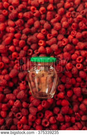 Empty Glass Jar For Raspberry Cooking, On The Texture Of Red Ripe Raspberry In The Background.