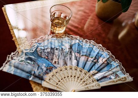 Hand-held Fan And A Glass Of Cognac On The Table.