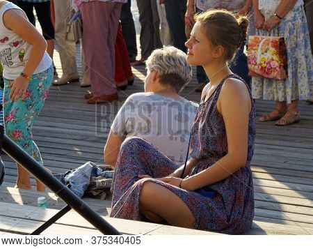 Moscow, Russia, Aug 12, 2017: Adult Girl Sitting Cross Legged On A Platform Among Other Visitors To