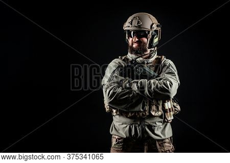 Portrait Of A Positive Soldier In A Military Uniform, A Commando Is Smiling On A Black Background, A