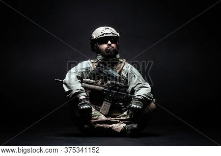 American Soldier In A Military Uniform With A Weapon Sitting Against A Black Background, Elite Troop