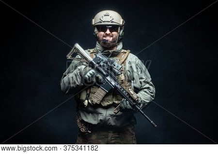 Soldier In Military Equipment With A Rifle Smiles At Night, A Commando In Uniform Against A Dark Bac