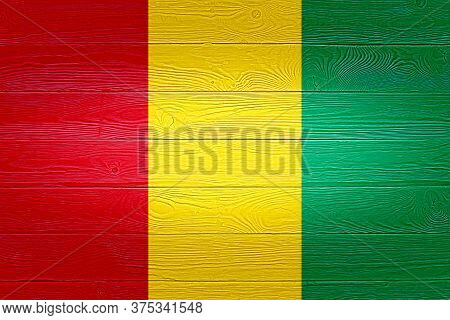 Guinea Flag Painted On Old Wood Plank Background. Brushed Wooden Board Texture. Wooden Texture Backg