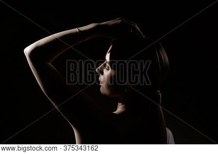 Portrait Of A Young Mysterious 25-year-old Girl With A Raised Hand On A Dark Background In Contour L