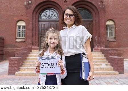 Start School, Female Teacher And Girl Student Together, School Building Background. Girl Holding Not