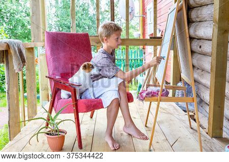 Caucasian Blond-haired Boy Sitting In A Chair With A Dog And Draws On An Easel With Pencils, Plein A