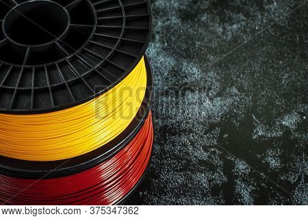 Filament For 3d Printing. Bright Thermoplastic Of Neon Yellow And Red Colors. Reel Horizontal View.