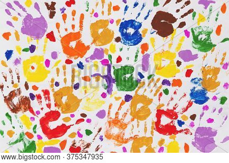 Colored Prints Of Childrens Hands On A White Canvas. A Childs Handprint On Paper. Colored Handprints