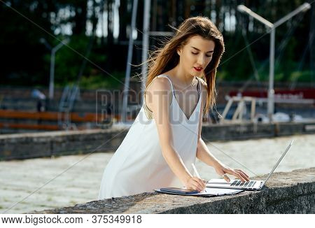 Beautiful, Serious Woman In A White Dress With A Tablet, Pen, Laptop Phone On The Dock