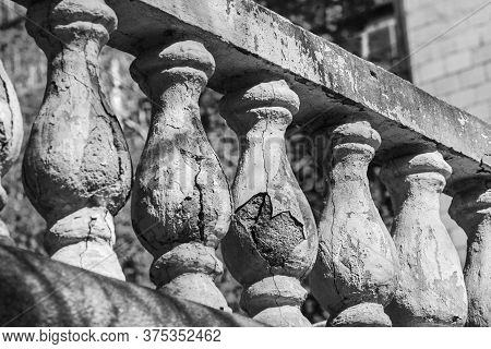 Old Stone Balusters At Sunny Rays In Day In Black And White
