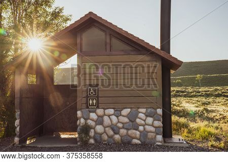 Rustic Pit Toliet Bathroom In Grand Teton National Park Wyoming, During Sunrise, With Beautiful Sunf