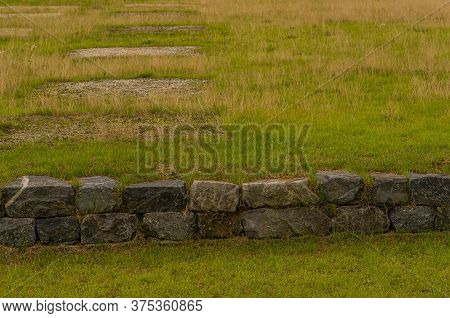 Large Square Slabs Of Stone In Ground At Archeological Site In Buyeo, South Korea.