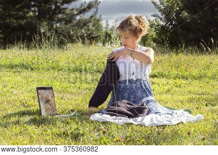 Woman Sits On The Grass In A Park Knitting Wool Clothes On A Knitting Needle And Shows A Knitted Det