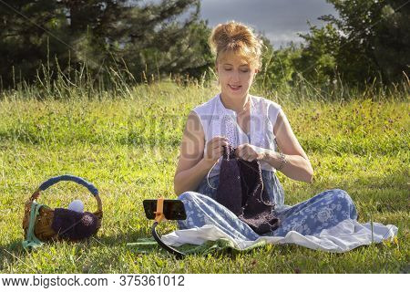 Woman Sits On The Grass In A Park Knitting Wool Clothes On Knitting Needles And Watches Lessons Or T