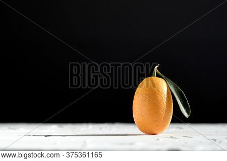 A Kumquat, A Small Exotic Citrus Fruit, With Its Leaf, On A White Textured Surface, On A Black Backg