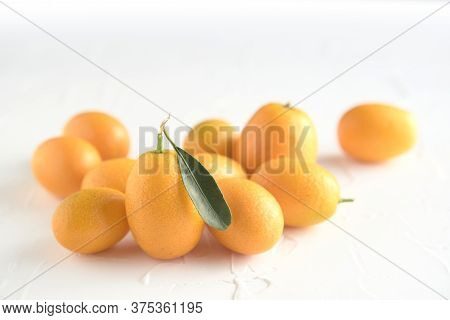 Fresh Kumquats, Small Exotic Citrus Fruits, On A White Textured Background
