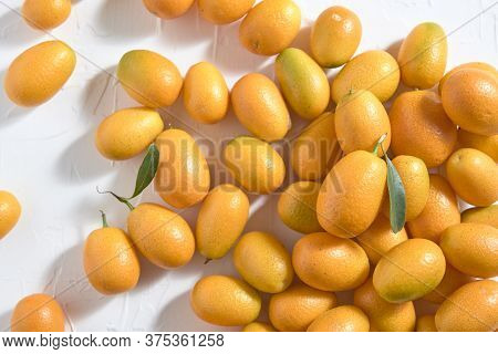 Fresh Kumquats, Small Exotic Citrus Fruits, On A White Textured Background. Top View.