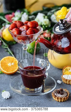 The Process Of Brewing Natural Tea With Strawberries, Tea Ceremony. A Cup Of Freshly Brewed Fruit Te