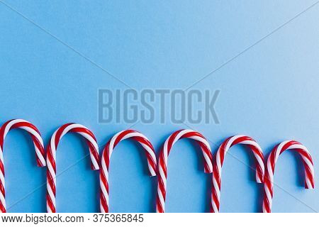Christmas Composition. Christmas Candy Canes In Row Flat Lay, Top View On Pastel Pink Background.hol