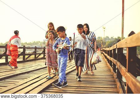 Kanchanaburi, Thailand - January 17, 2020 : Thai Parents With Their Kids Are Walking On The Famous T