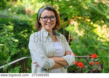 Portrait Of Happy Middle-aged Woman, Confident Smiling Female With Folded Arms On Home Outdoor Lands