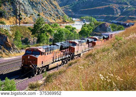 July 7, 2020 In Cajon Pass, Ca:  Bnsf Locomotives Pulling Rail Cars Full Of Cargo Up Mountainous Ter