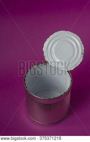 Empty Open Tin Can On A Purple Background. Round Jar With Enamelled Inner Coating For Food. Creative