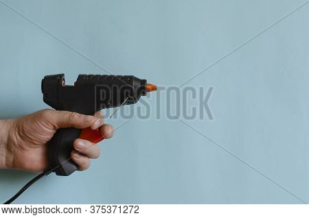 Glue Thermo Gun In A Male Hand. An Electric Device For Gluing Objects With Sticks Of Glue. Middle-ag
