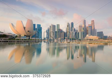 Singapore cityscape at early morning with real reflections on sea water. Landscape of Singapore business building around popular Marina bay with skyscapers. Singapore city