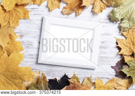 Blank Rectangular Photo Frame Lies On Vintage Wooden Desk With Bright Autumn Foliage. Flat Lay With