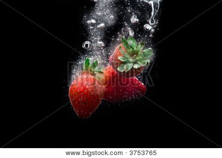 Close up view of fresh strawberries gurgling through the water poster