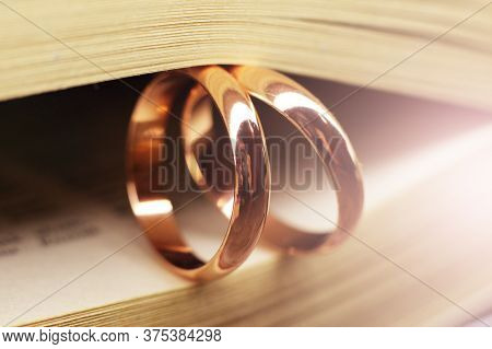 Two Wedding Rings On A Book So Close