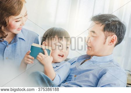 Asian Father Mother And Child Are Reading Book Wearing Blue Shirt Posing For In Bedroom In White Roo