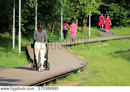People Walking On A Wooden Path In Summer Park, Leisure Outdoors. Slim Woman With A Baby Stroller, C