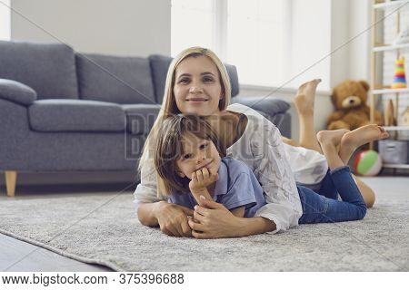 Loving Mother Hugging Her Son While Lying On Carpet In Living Room. Parent And Child Embracing At Ho