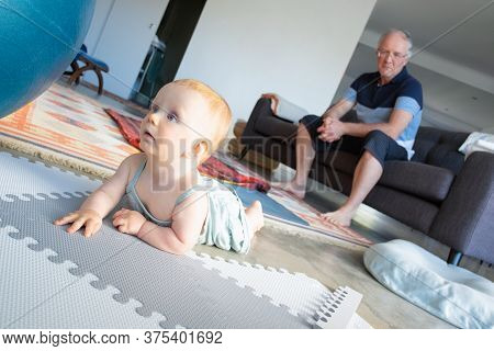 Cute Red-haired Newborn Lying On Belly And Looking Away With Open Mouth. Baby On Floor. Serious Gran