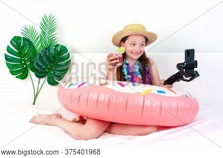 Little Girl Blogger Imitates Vacation Sitting On The Bed At Home, Removes The Vlog. A Child In A Swi