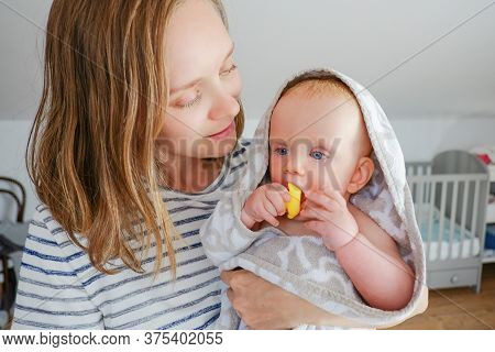Positive Mom Holding Sweet Dry Baby Wearing Hooded Towel After Shower And Biting Rubber Bathing Toy.