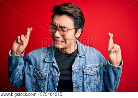 Young handsome chinese man wearing denim jacket and glasses over red background gesturing finger crossed smiling with hope and eyes closed. Luck and superstitious concept.
