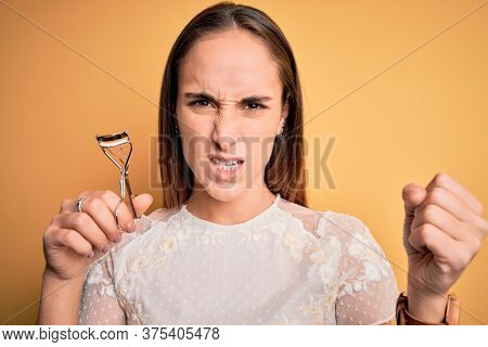 Young beautiful woman using eyelash curler standing over isolated yellow background annoyed and frustrated shouting with anger, crazy and yelling with raised hand, anger concept