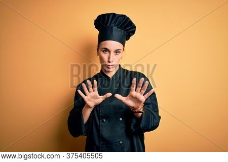 Young beautiful chef woman wearing cooker uniform and hat standing over yellow background Moving away hands palms showing refusal and denial with afraid and disgusting expression. Stop and forbidden.