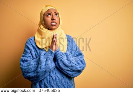 Young African American afro woman wearing muslim hijab over isolated yellow background begging and praying with hands together with hope expression on face very emotional and worried. Begging.