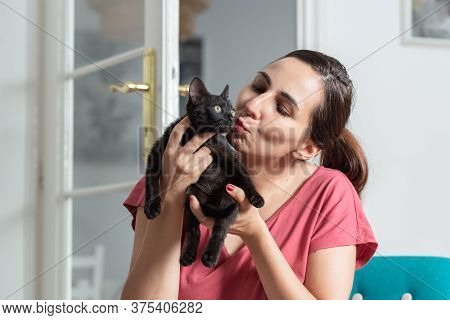 Woman Kissing Her Kitten. Domestic Lifestyle. Woman Relaxing On Chair With Kitten. Hipster Lifestyle